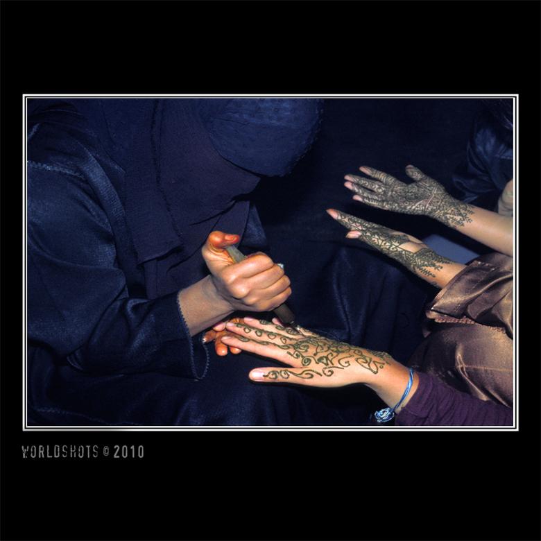 henna handen - donkere gesluierde Marokkaanse vrouwen zijn maar wat gretig om tegen betaling nietsvermoedende toeristen de handen te beschilderen met