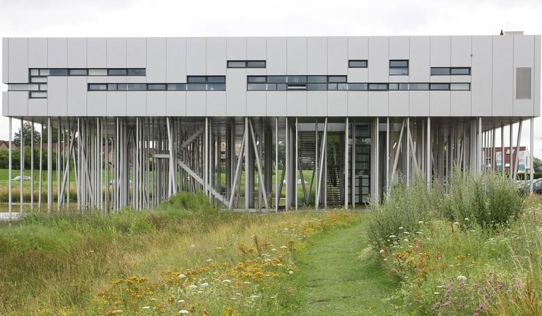Huis op palen. - <br /> Gebouw (optiekcentrum) gebouwd op tientallen schots en scheef staande aluminium palen. In de plaats Houten.