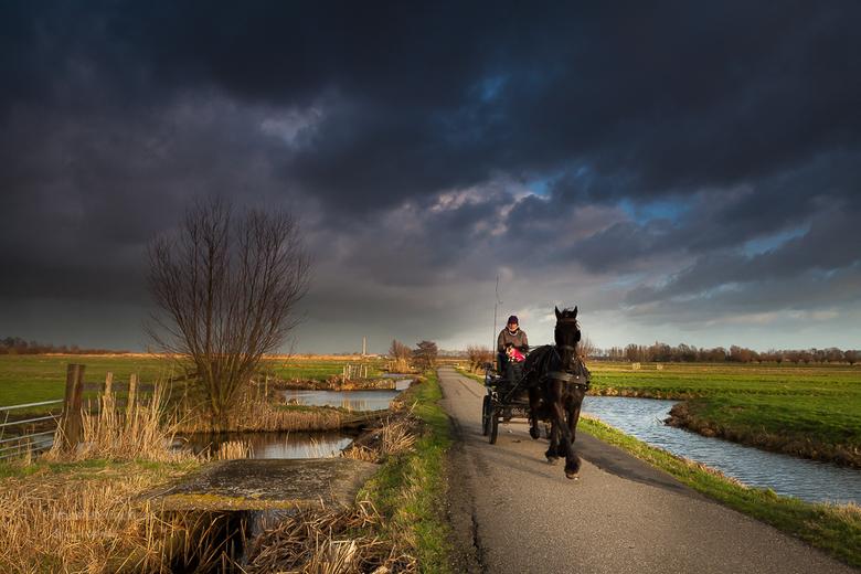 De Krimpenerwaard 80 - Een koude onstuimige winterdag in de polder . Indrukwekkende dreigende luchten , waaruit felle buien regen en hagel naar benede