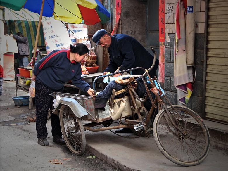Groenteboer - In een kein plattelandsstadje in China - Kaifeng - is het leven op straat. Overal is wel wat te zien. Hier is een een groenteboer met zi