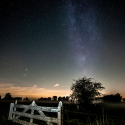 Milky Way with lit fence