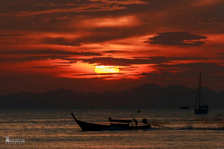 Krabi - Thailand - Een longtailboot tijdens zonsondergang bij Ao Nang Beach in Thailand.