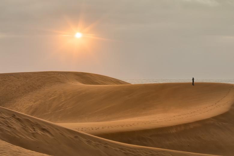 Dunas de Maspalomas - De Dunas de Maspalomas. Boven de horizon hing een donkere wolkenband, maar de zon wist er toch even door heen te prikken.