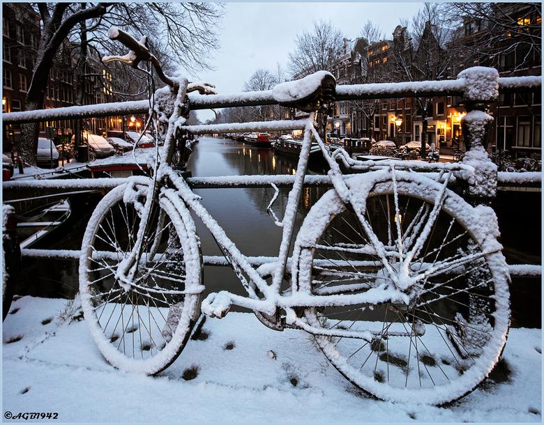 Fiets. - Besneeuwde fiets op brug.