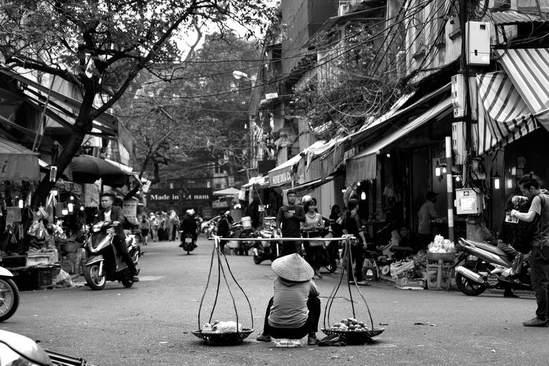 Stadsuitzicht - Een kijkje in de straten van hanoi in Vietnam. Een verkoopster van groenten neemt even een rustpauze midden op straat.