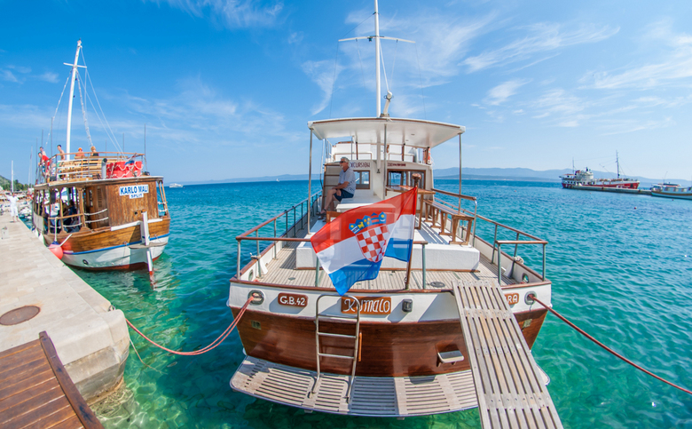 Croatia boat - Een skipper zit rustig in het zonnetje te relaxen op zijn boot.