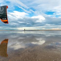 Kitesurfer met spiegeling van de lucht
