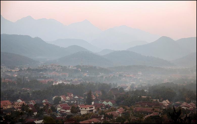 zon net onder - de zon is net achter de bergen verdwenen en de lucht kleurt nog roze na boven het prachtige karstgebergte in Luang Prabang Laos