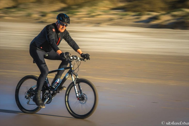 eerste meegetrokken in beweging foto - Een mountainbiker op het strand geprobeerd te bevriezen.