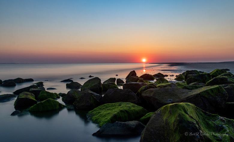 Sunset  - Deze foto is gemaakt aan de westkust van Ameland.<br /> De op de voorgrond liggende stenen zijn bedekt met zeewier hetgeen een bijzonder ef