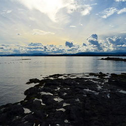 Wolkenpartijen, stenen en water