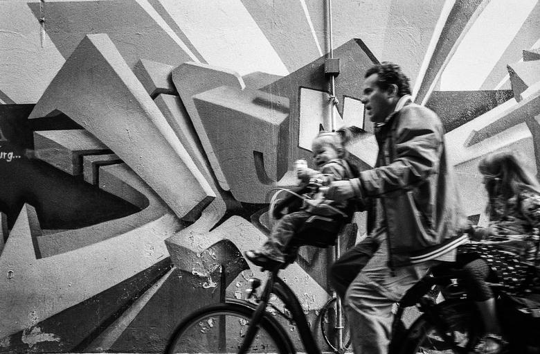 No happy family - Pa met de kids op de fiets, kinderen huilen, pa met een lang gezicht...toch had het wel iets, de grafitty maakte het af.<br /> <br