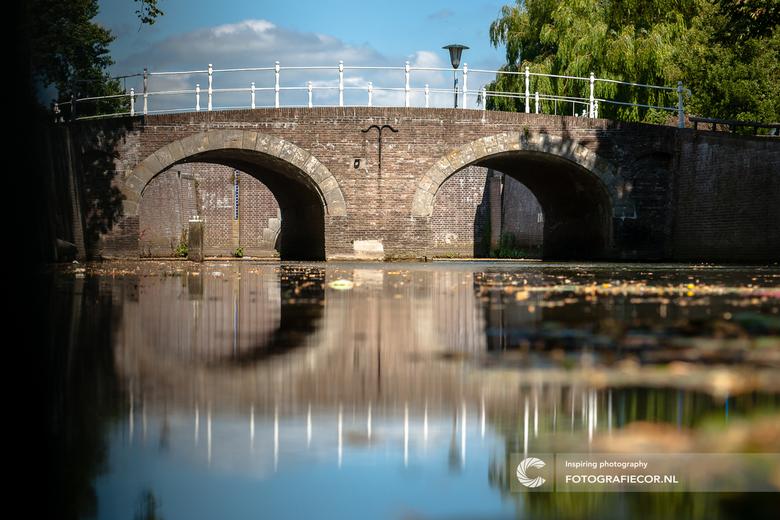 Spiegelend in de oude stadsgracht - Een van enige overgebleven oude bruggen over de stadsgracht van de hanzestad Kampen. In de jaren zestig hebben de