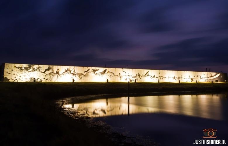 T Skildermuurtje - &quot;T Skildermuurtje&quot; het grootste kunstwerk van Werelderfgoed de Wadden tijdens het blauwe uur in Oudeschild op Texel.<br /