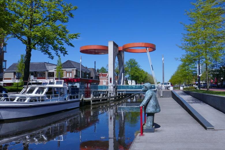 Krinkiespijer (Kringetjesspuwer) - Met op de achtergrond de bijzondere Eurobrug staat langs het Stadskanaal een bronzen beeld van Toos Hagenaars: de k