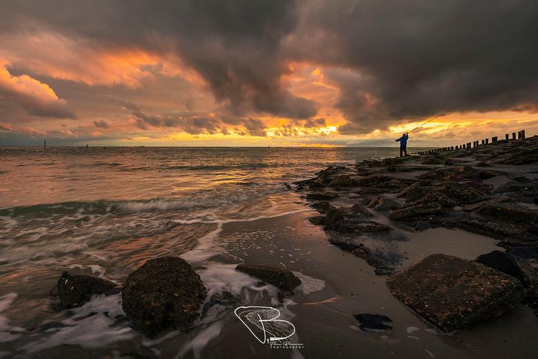 Gone Fishing - Een visser onder dreigende wolkenlucht bij Westkapelle, waar de laatste zonnestralen door het zeewater bereiken.