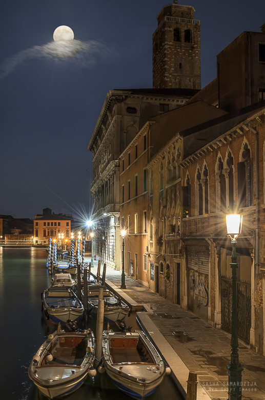 Moonlight in Venice - Anchored boats in Venice canal, street lit by lamps and full moon, with moving clouds, green water reflection