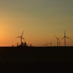 Ondergaande zon met de windmolens van Delfzijl in de horizon
