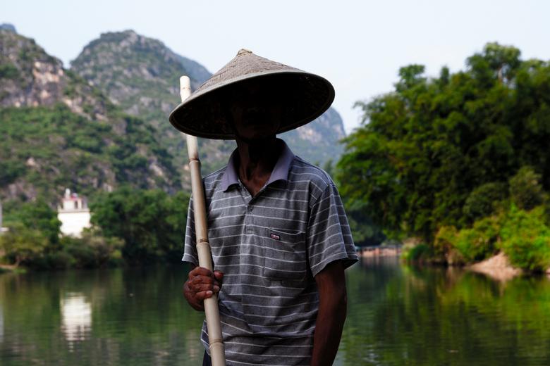 Man met verborgen gezicht - Op een smal bamboo bootje vaarde hij met ons door rivieren in Guiling (China). <br /> <br /> Ik wilde graag 1 foto van h