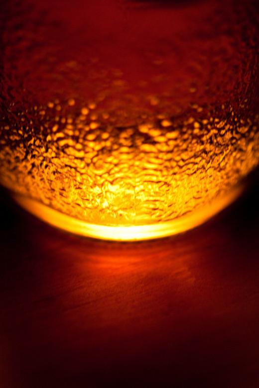 Rara . . . - onderkant Crodino flesje met inhoud op hout, glanzend tafel.