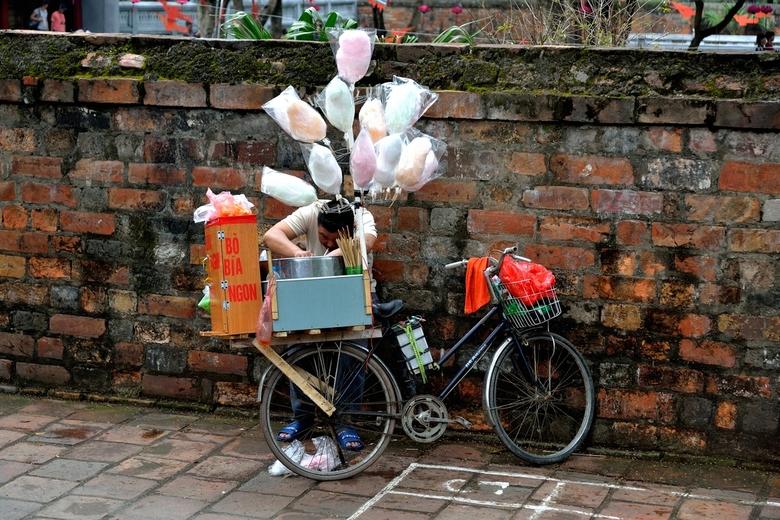 Snoepgoed - Een mooi plaatje, een verkoper met zijn fiets met snoepgoed en suikerspinnen in de straten van hanoi, vietnam.