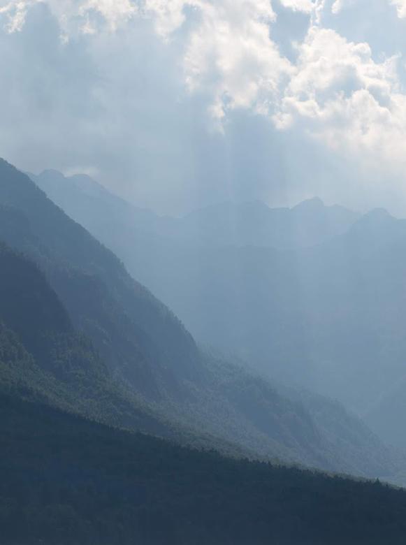 Bergen in nevel - Bergen in nevels met zonlicht door wolken