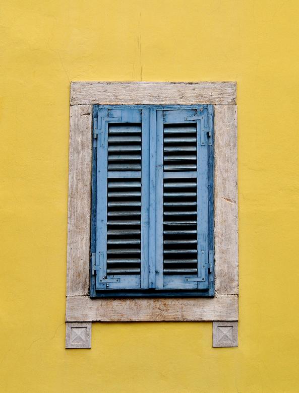 windows closed - gesloten blauwe luiken in en klanlgele gevel