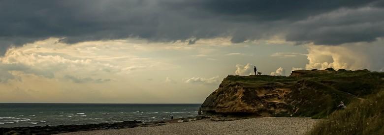 Man met hond - Silhouet van een man die zijn hond uitlaat op een rotspunt aan de Normandische kust tegen een achtergrond van prachtige wolken en zonso