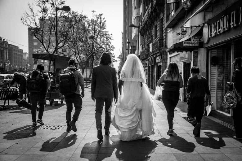 Foto's voor het verse bruidspaar - Een bruidspaar en hun entourage onderweg naar een nieuwe locatie voor hun bruidsfoto's in Mexico-Stad.