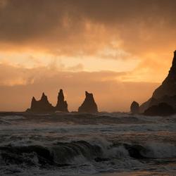 Prachtig uitzicht op de ruwe zee en de 'drie trollen' bij Dyrhólaey in IJsland net voor een enorme hagelbui losbarstte