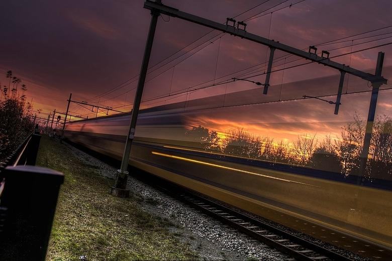Temporarily Transparent Train - Een kleurrijke zonsondergang vandaag. De trein rijdt in volle vaart voorbij, snel genoeg om transparant te zijn.