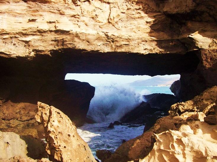 Het wilde water - Door het oog van een mooie rotspartij op Fuerteventura, Canarische eilanden