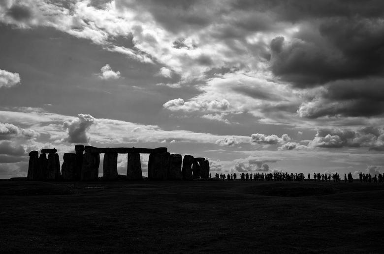People at Stonehenge - Tegenlicht van de rij toeristen die geduldig wacht om naderbij de stenen van Stonehenge te komen.