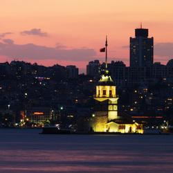 Ondergaande zon in Istanbul met verlichte Leandertoren