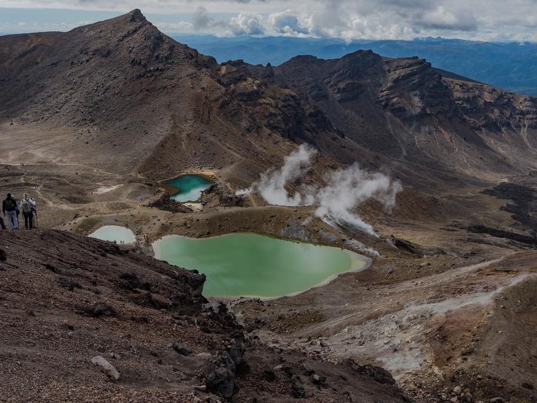 tonga2 - Ongeveer halverwege de Tongariro Crossing, iets boven de 2000 meter hoogte krijg je dit uitzicht op een drietal meertjes. Van veraf lijken de
