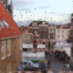 Markt Delft vanachter het beregende raam