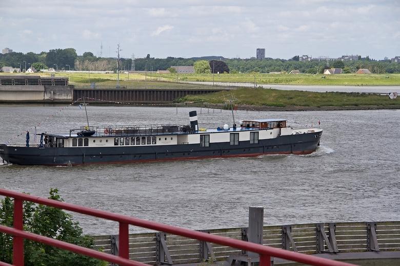 Een woonboot of kleine hotelboot. - Even later voer dit voertuig door de open brug. Het lijkt op een vrachtschip dat omgebouwd is tot ruime woonboot o