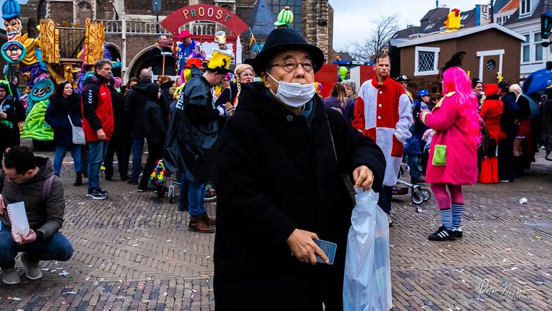 carnaval - Een ietwat verdwaasde toerist op een plein vol carnaval.