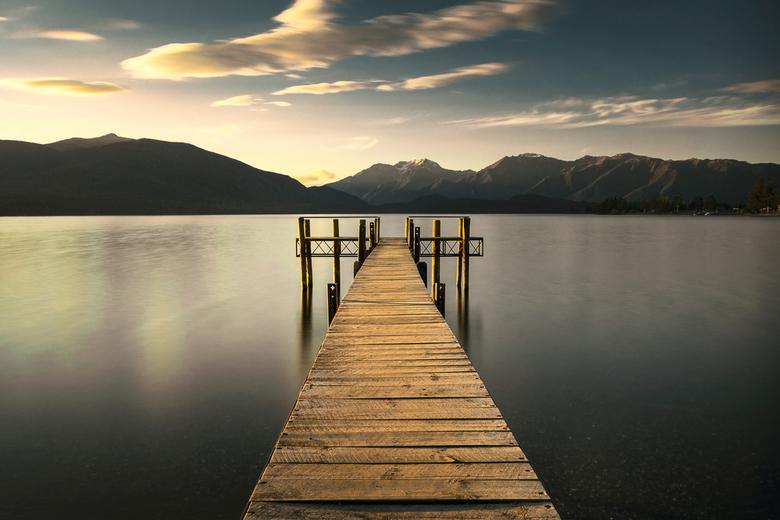 Tranquility - De steiger in het meer van Te Anau, Nieuw Zeeland, verlicht in een gouden gloed voordat de zon ondergaat achter de omliggende bergen.