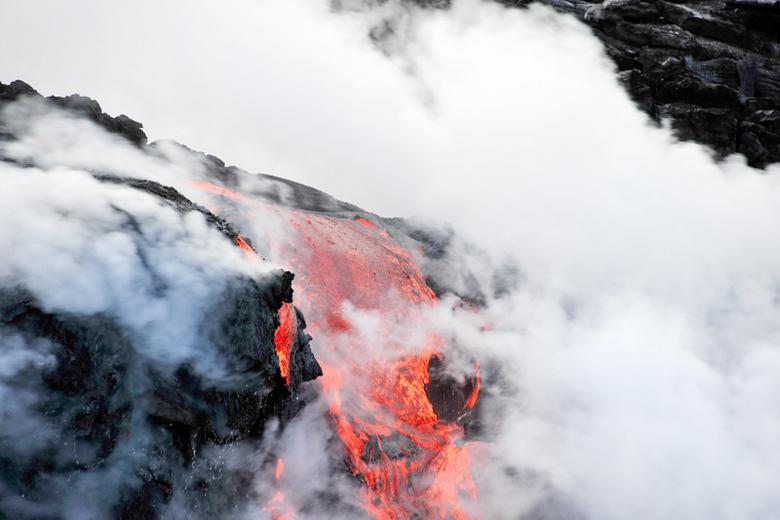 Lava van de vulkaan Kilauea. - Genomen vanuit een bootje, lava die in de zee stroomt.