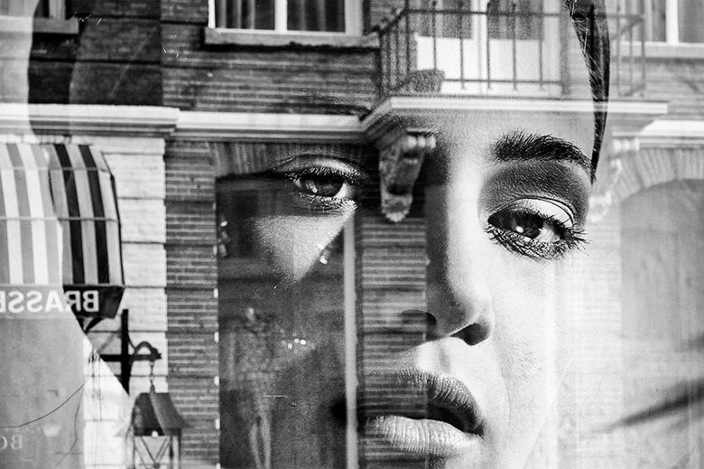 You're being watched 11 - Bij het zien van deze reflectie in een etalageruit van een boutique viel mij de enigszins melancholische blik van de dame op