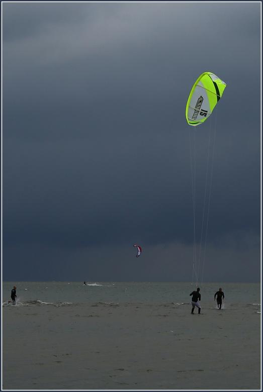 Kitesurfing - Beeld van kitesurfers vlak voor het noodweer losbarst. Ze schijnen niet veel oog te hebben voor de aanstaande bui. Hoewel, één van hen l