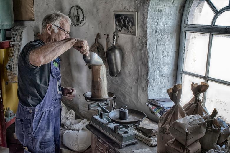 Schepje er boven op - Heb in Cadzand-Bad een serie gemaakt van de molen aldaar. De molenaar schept griesmeel en weegt deze af.