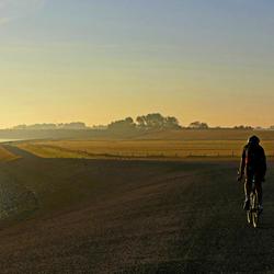 Mountainbiker in de gloed van zonsopgang langs het Wad bij Stroe.