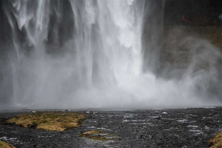 Seljalandsfoss - Alles wordt nat van de stuifregen door de waterval, ook de camera. Fotograferen moet snel of van ver af. Ook op deze sombere dag is h