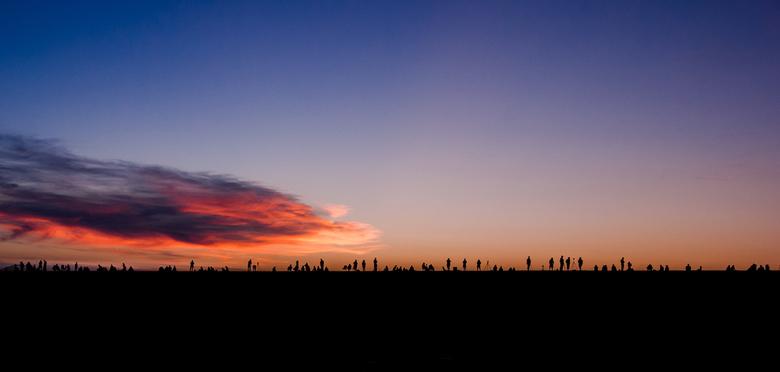Fotografen op de dijk - We kijken hier naar een silhouet van een groep fotografen op de dijk bij Lauwersoog. De zon gaat onder achter de rug van deze