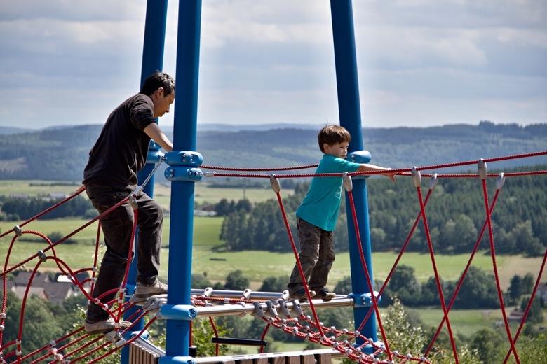 Vader en zoon op een klimtoren.