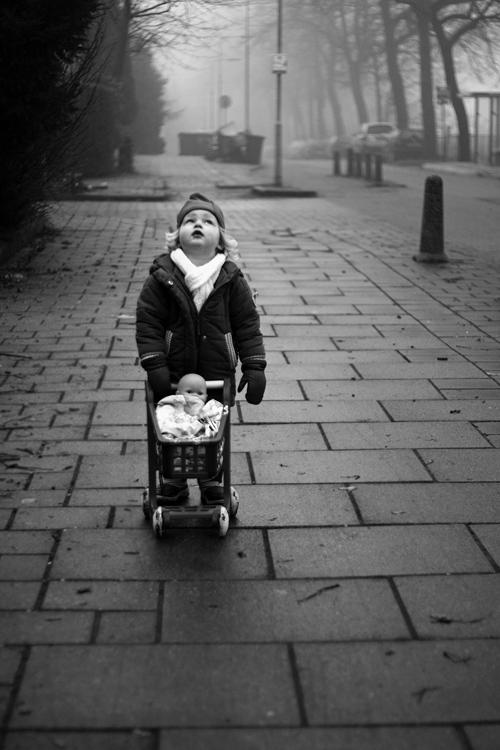 What's happening? - een kind met een poppenwagen kijkt naar boven, zwart-wit
